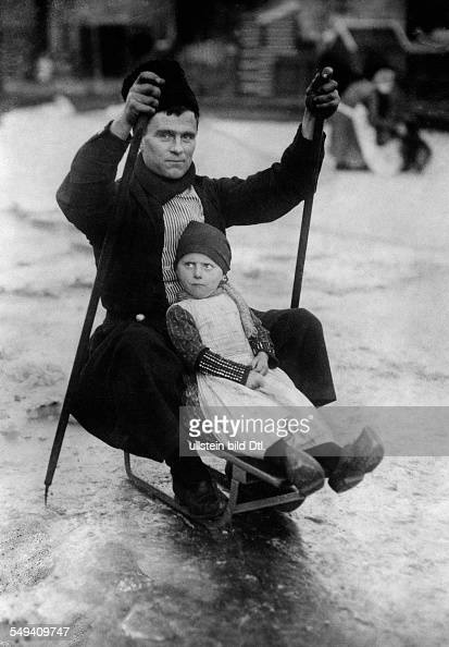 Netherlands father skating with his daughter on a sledge over the ice 1919 Photographer Sennecke Published by 'Das Blatt der Hausfrau' 24/1923...