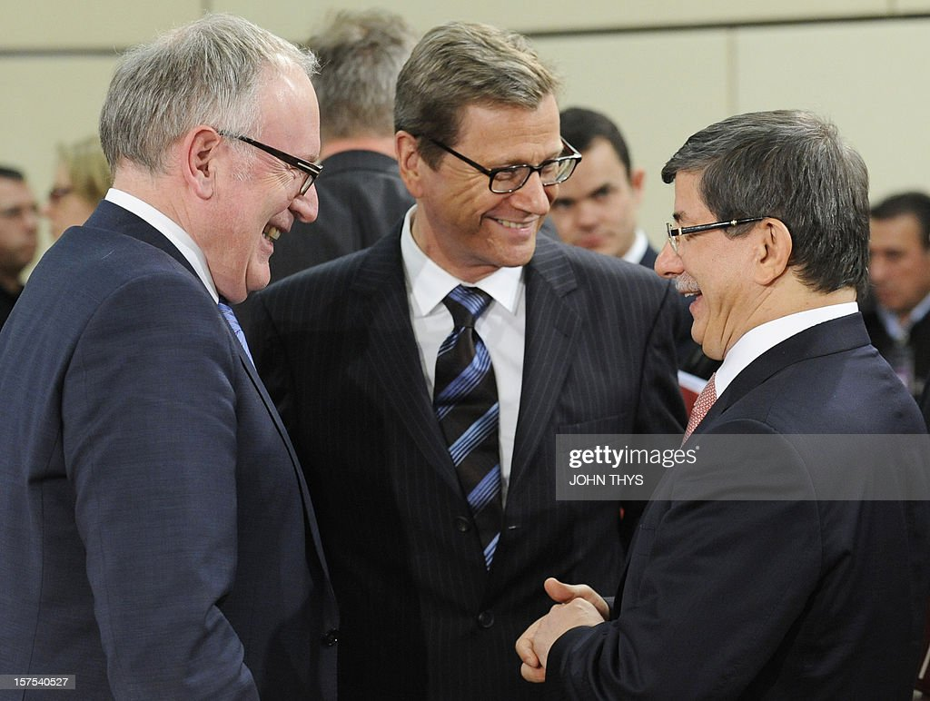 Netherlands' Foreign Minister Frans Timmermans (L) laughs with Germany's Foreign Minister Guido Westerwelle (C) and Turkey's Foreign Minister Ahmet Davutoglu (R) during a meeting of foreign affairs ministers from the 28 North Atlantic Treaty Organization (NATO) member-countries to discuss Syria and Turkey's request for Patriot missiles to be deployed protectively on the Turkish-Syrian border at the NATO Headquarters in Brussels, on December 4, 2012.
