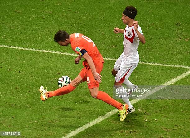 Netherlands' forward and captain Robin van Persie misses a shot past to Costa Rica's midfielder Christian Bolanos during a quarterfinal football...