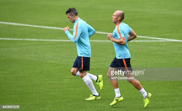 Netherlands' forwards Arjen Robben and Robin van Persie run during a training session with teammates at the Stade de France in SaintDenis north of...