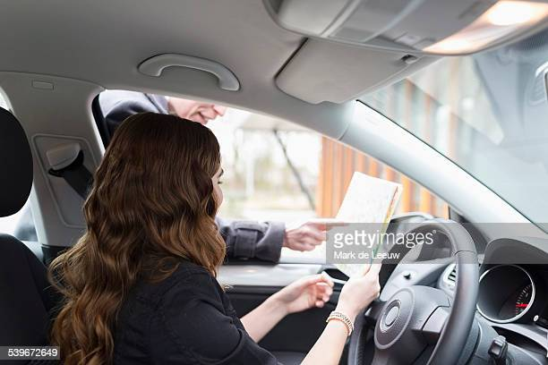 Netherlands, Goirle, Man giving directions to young woman in car