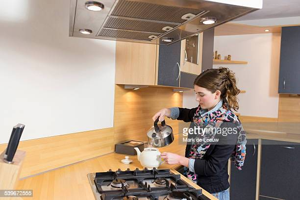 Netherlands, Goirle, Woman pouring water at teapot in kitchen