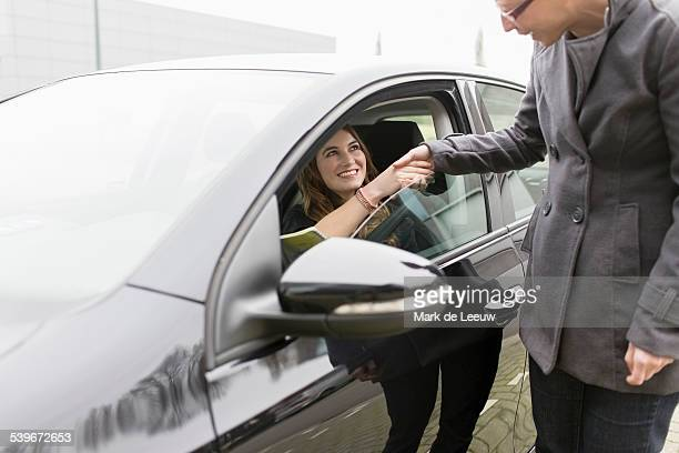 Netherlands, Goirle, Women shaking hands through open car window