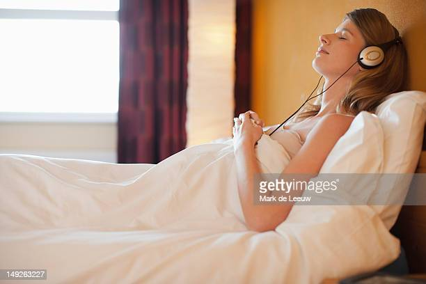Netherlands, Goirle, Young pregnant woman listening to music in bed