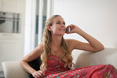 Netherlands, Helvoirt, Woman in dress sitting on sofa and using phone