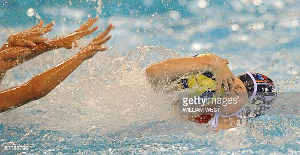 Netherlands' Lefke van Belkum keeps the ball safe from the hands of Greece's players during their women's preliminary round group B water polo match...