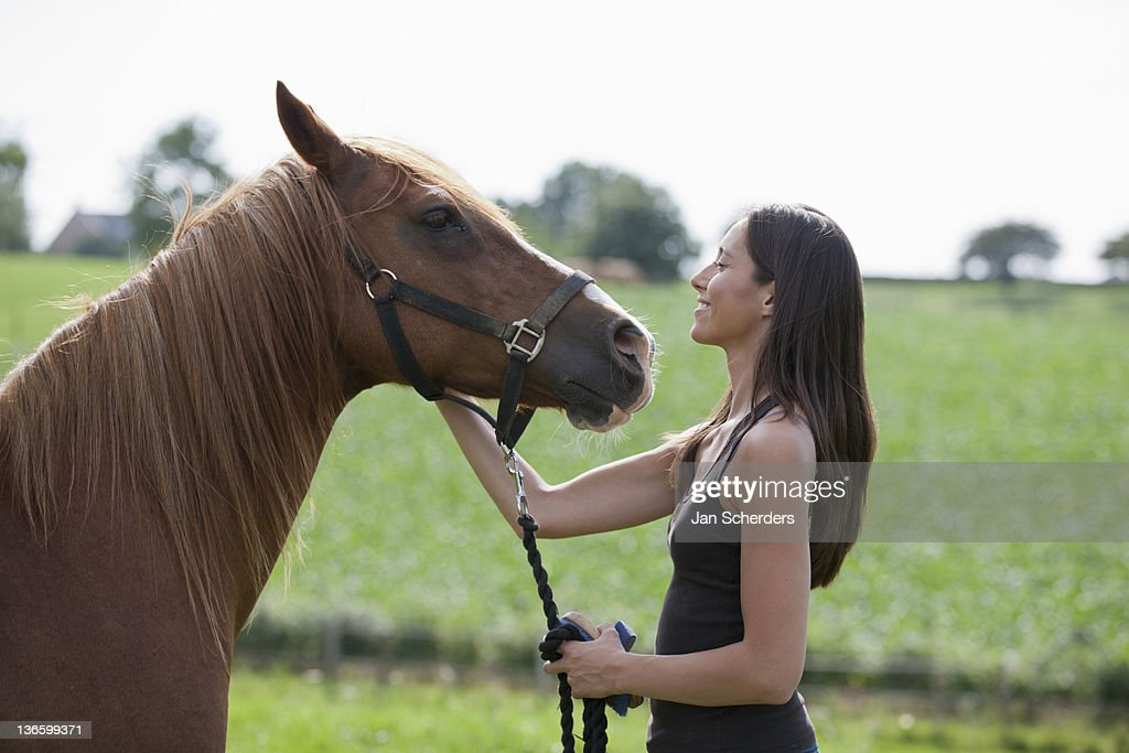 Netherlands, Maastricht, Young woman with horse in field : Stock Photo