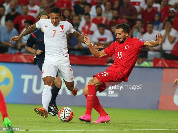 Netherland's Memphis Depay vies for the ball with Turkey's Mehmet Topal during the Euro 2016 qualifying match between Turkey and Netherlands at the...
