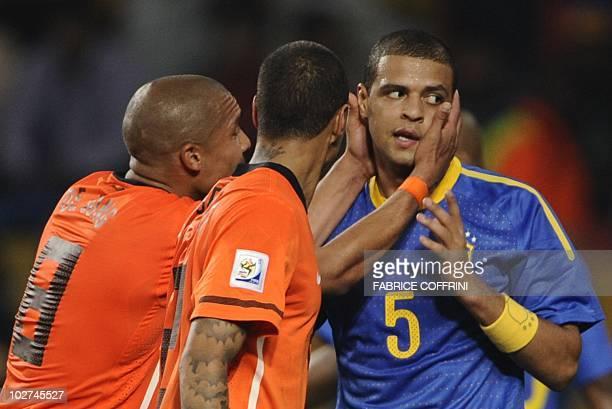 Netherlands' midfielder Nigel de Jong touches Brazil's midfielder Felipe Melo after he committed a foul on Netherlands' striker Arjen Robben and got...