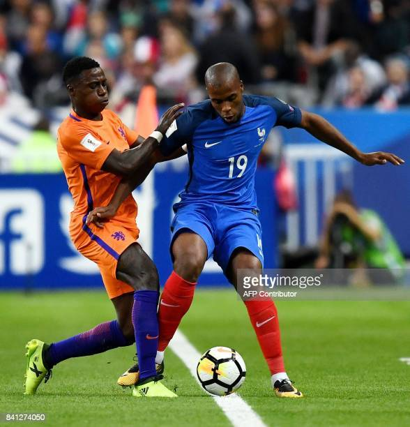 Netherlands' midfielder Timothy FosuMensah fights for the ball with France's defender Djibril Sidibe during the 2018 FIFA World Cup qualifying...