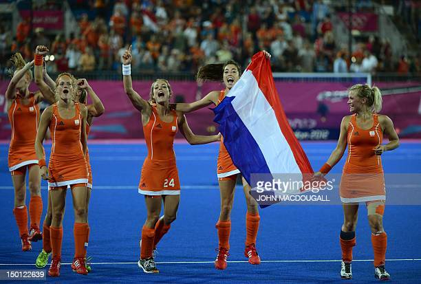 Netherlands Naomi van As and Netherlands Eva de Goede wave their national flag as they celebrate after victory in the women's field hockey gold medal...