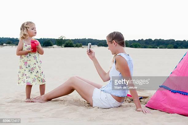 Netherlands, Nationaal Park De Loonse en Drunense Duinen, Mother taking picture of daughter (2-3) on beach