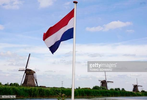 Netherlands national flag is pictured next to historical windmills in the village of Kinderdijk southeast of Rotterdam on July 26 2017 / AFP PHOTO /...
