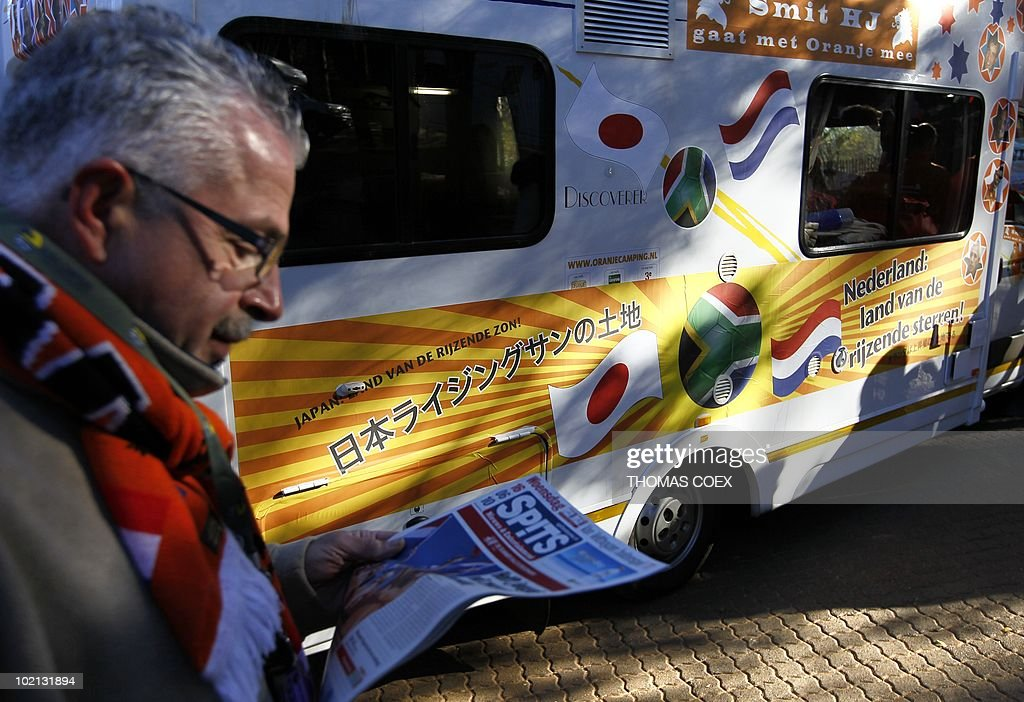 A Netherlands national football team supporter reads a Dutch newspaper next to a motorhome that reads 'Japan: Land of the Rising Sun' (C) and 'Netherlands: Land of the Rising Star' (R) before driving in a convoy of 140 'orange' vehicles from their Fountainvalley camp, northern Johannesburg on June 16, 2010. Around 700 Dutch fans will move from Johannesburg to Durban, the city where their team will play their second 2010 World Cup football match against Japan.