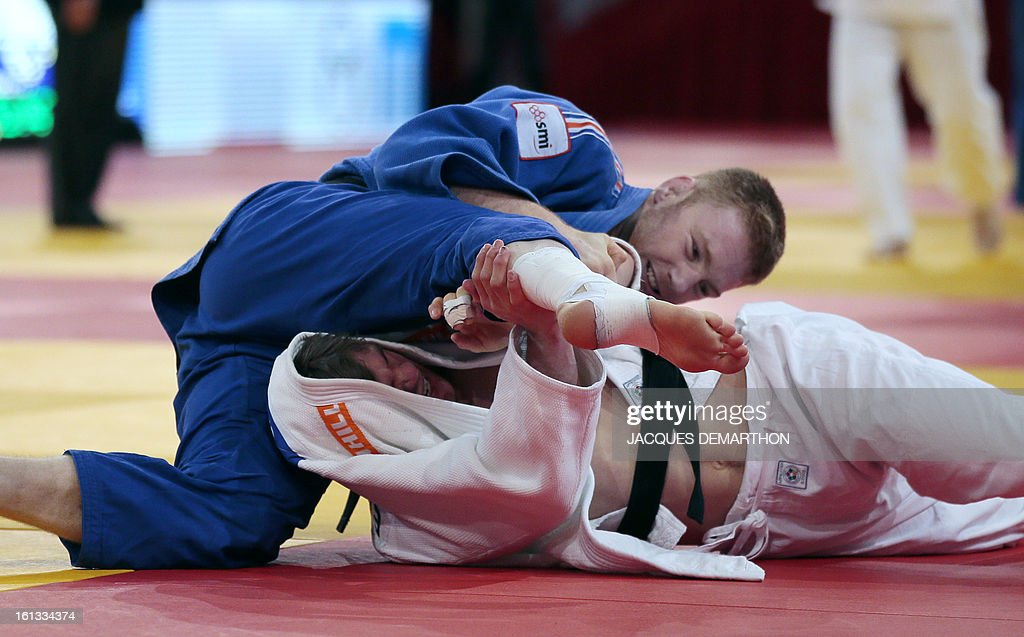 Netherland's Noel van't End (white) fights against France's Axel Clerget (blue) on February 10, 2013 in Paris, during the eliminatories of the Men -90kg of the Paris Judo Grand Slam tournament.