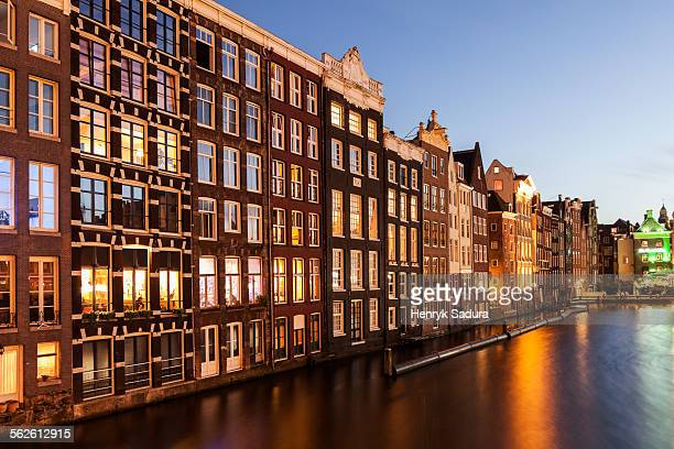 Netherlands, North Holland, Amsterdam, Buildings by canal at sunrise