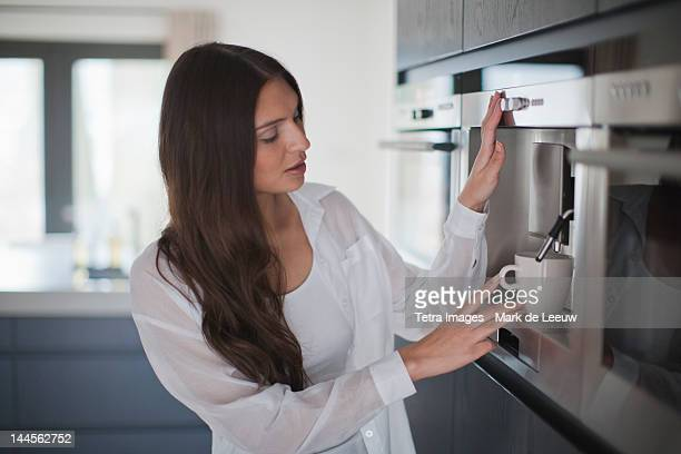 Netherlands, Oisterwijk, Young woman making coffee