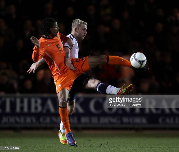 Netherlands' Patrick Van Aanholt battles for possession of the ball with Scotland's Johnathon Russell