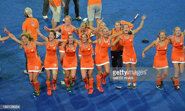 Netherlands players celebrate with their coaches after victory in the women's field hockey gold medal match between Netherlands and Argentina at The...