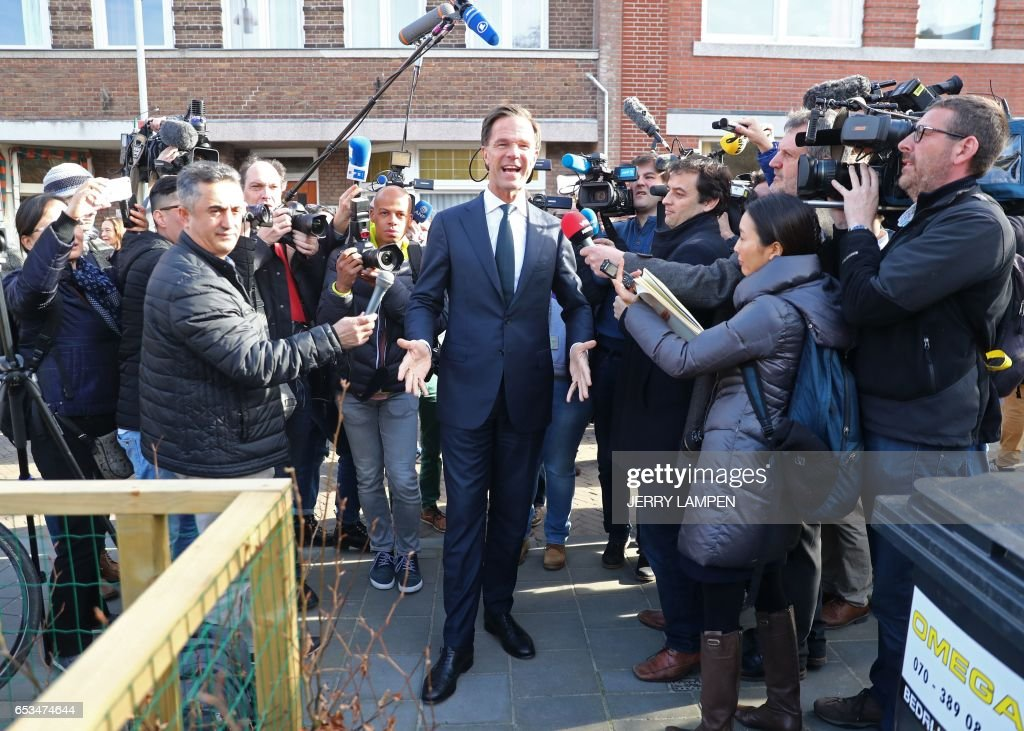TOPSHOT - Netherlands' prime minister and VVD party leader Mark Rutte (C) arrives to cast his ballot for Dutch general elections at a polling station on March 15, 2017 in The Hague. Millions of Dutch voters were going to the polls March 15 in key elections overshadowed by a blazing diplomatic row with Turkey, with all eyes on the fate of far-right MP Geert Wilders. Following last year's shock Brexit vote, and Donald Trump's victory in the US presidential polls, the Dutch general elections are seen as a litmus test of the strength of far-right and populist parties ahead of other ballots in Europe this year. / AFP PHOTO / ANP / Jerry Lampen / Netherlands OUT