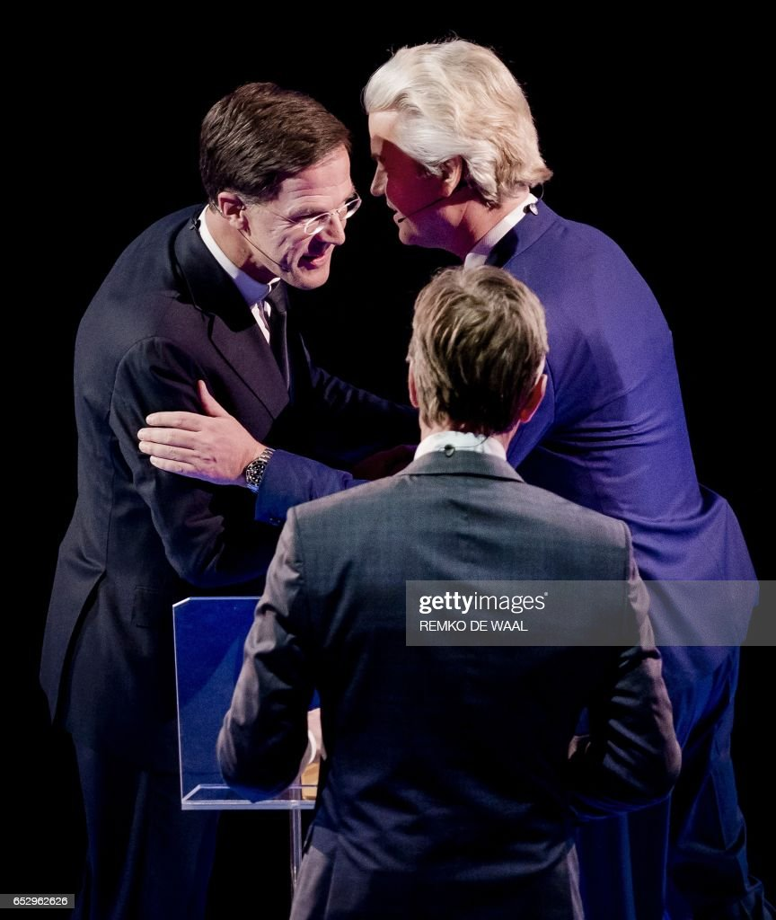 Netherlands' prime minister Mark Rutte of the VVD Liberal party (R) and Netherlands' far-right politician Geert Wilders of the PVV party shake before a debate on March 13, 2017 in Rotterdam, prior to March 15 Dutch parliamentary elections. / AFP PHOTO / ANP / Remko de Waal / Netherlands OUT