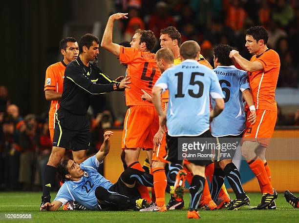 Netherlands protest to Referee Ravshan Irmatov as Martin Caceres of Uruguay lies on the ground during the 2010 FIFA World Cup South Africa Semi Final...