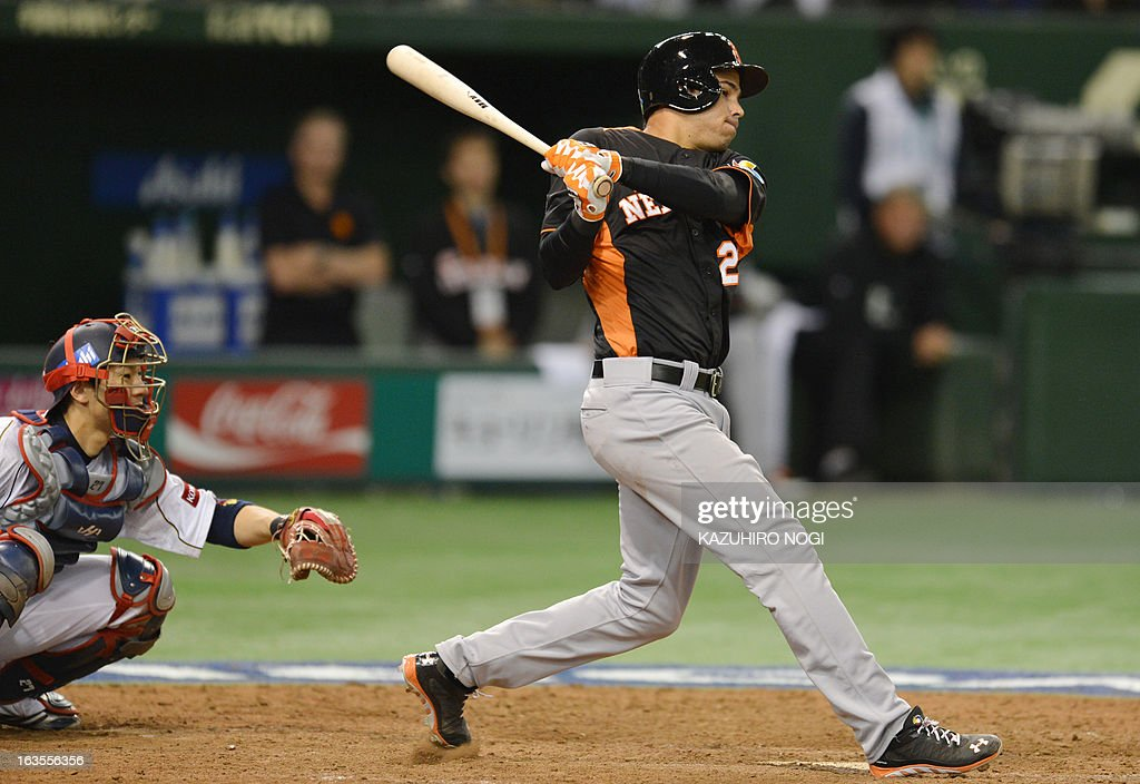 Netherlands' Quintin De Cuba bats a timely single hit as Japan's catcher Ryoji Aikawa (L) looks on during the eighth inning of their second-round Pool 1 game in the World Baseball Classic tournament at Tokyo Dome on March 12, 2013. Japan beat the Netherlands 10-6.