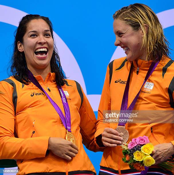 Netherlands' Ranomi Kromowidjojo poses on the podium with the gold medal flanked by bronze medalist Netherlands' Marleen Veldhuis after winning the...