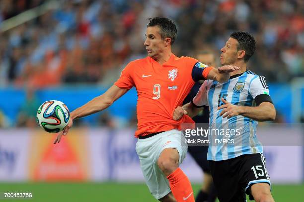 Netherlands' Robin van Persie battles for the ball with Argentina's Martin Demichelis