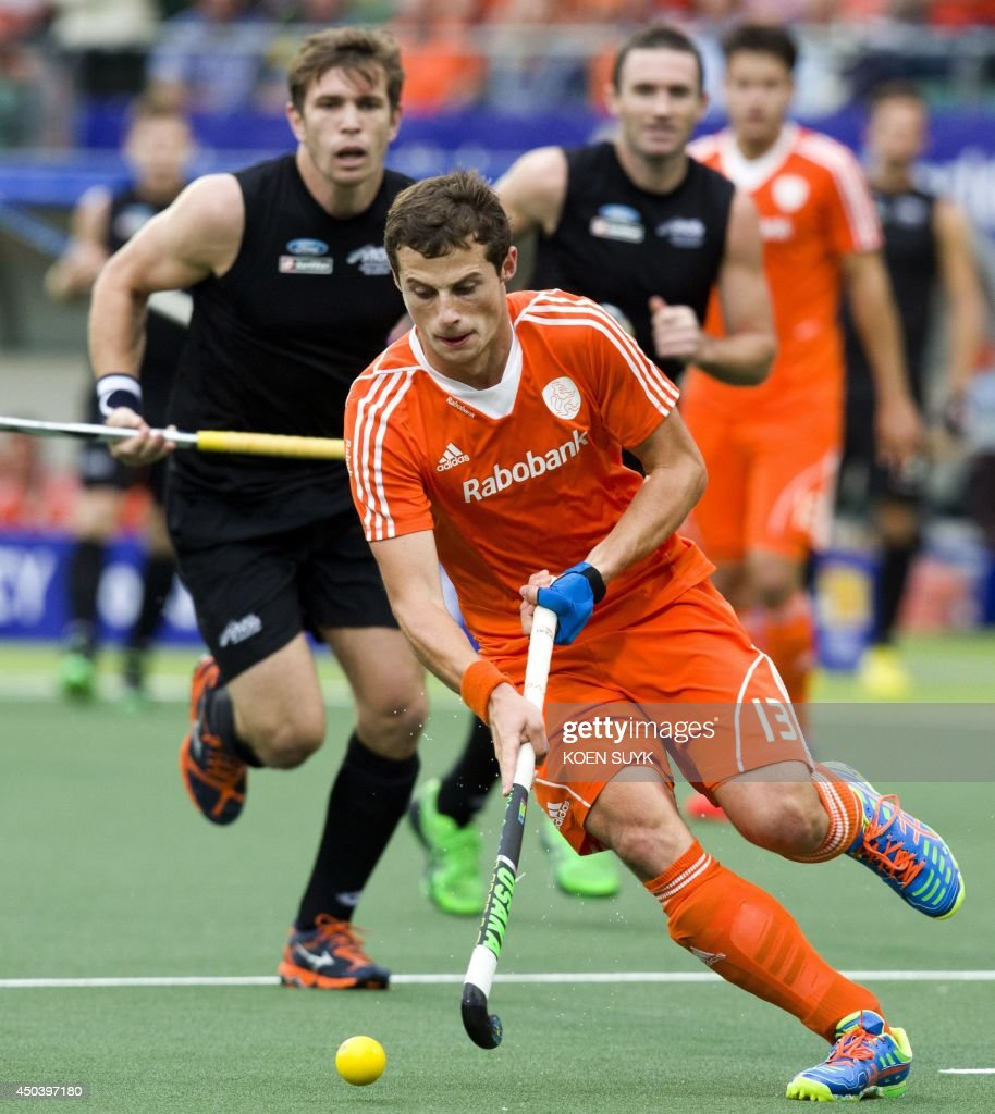 Netherlands' Sander Baart (C) runs with the ball during the stage group match between Netherlands' and New Zealand of the men's tournament of the 2014 Field Hockey World Cup in The Hague, on June 10, 2014. AFP PHOTO / ANP / KOEN SUYK **NETHERLANDS OUT**