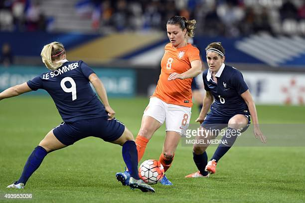 Netherland's Sherida Spitse vies with French forward Eugenie Le Sommier and French midfielder Charlotte Bilbault during the women's friendly football...
