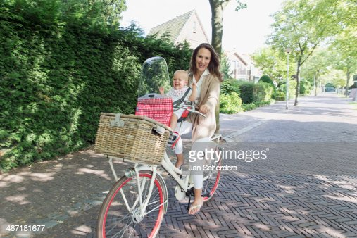 Netherlands, South Holland, Oud-Beijerland, Mother with her baby daughter (12-17 months) on bicycle