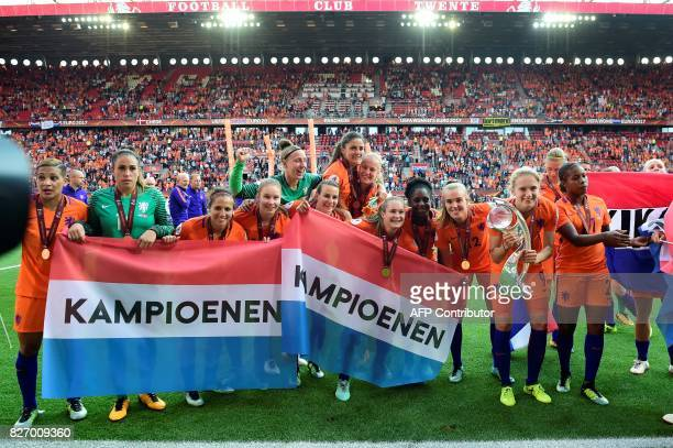 Netherlands' team players celebrate with the trophy and Dutch national flags reading 'champions' after winning the UEFA Womens Euro 2017 football...