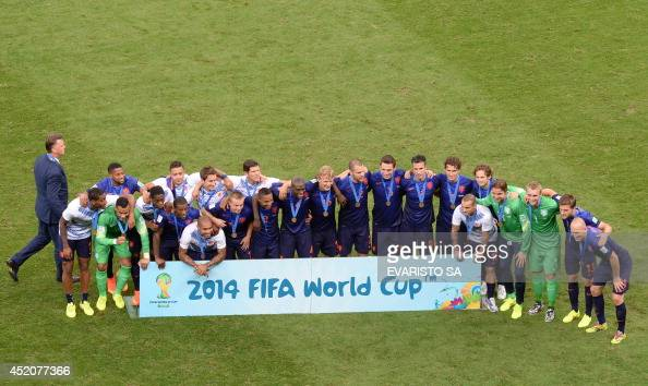 Netherlands' team pose for a group photo with their bronze medals after winning the third place playoff football match between Brazil and Netherlands...