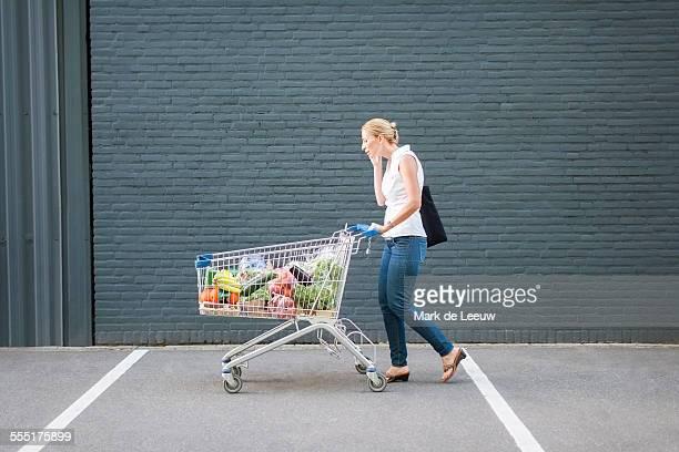 Netherlands, Tilburg, Woman walking with shopping cart