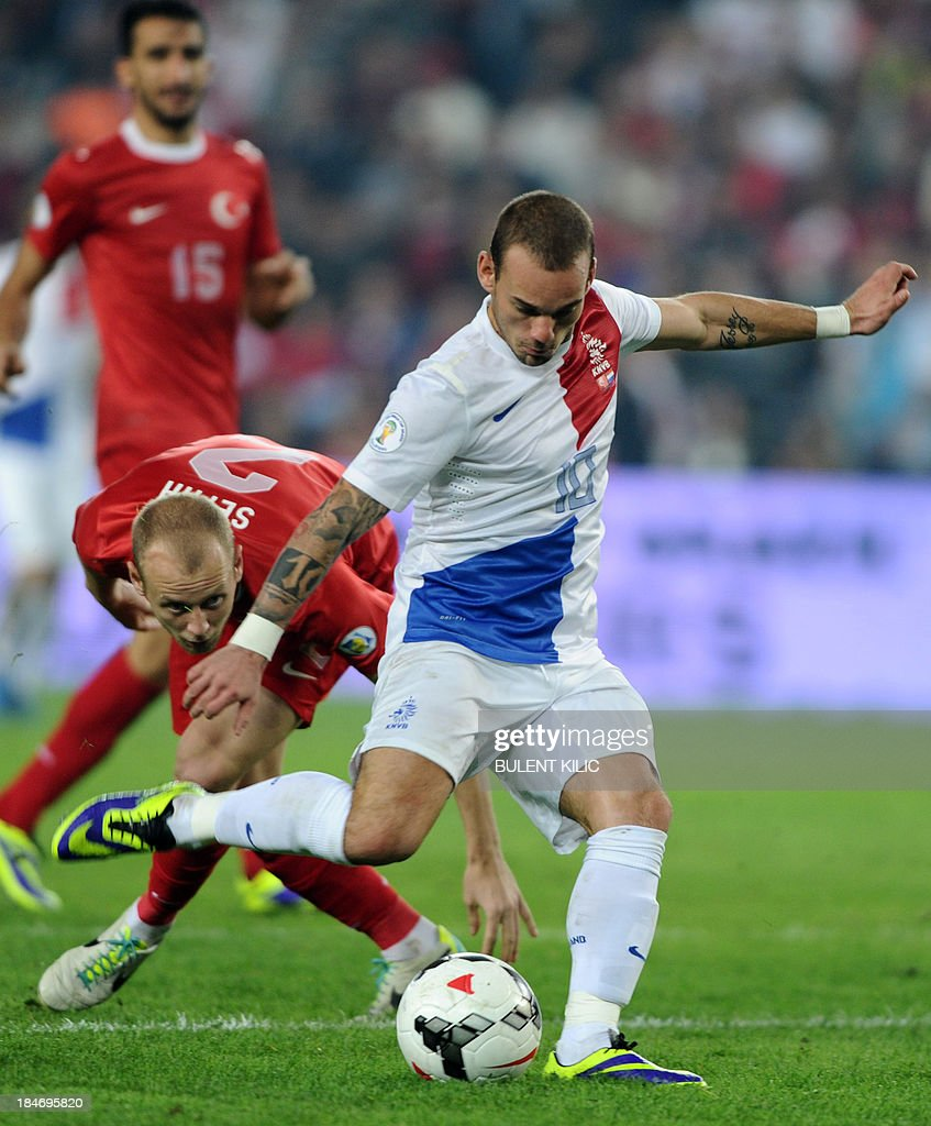 Netherlands' Wesley Sneijder kicks (R) his goal against Turkey during the 2014 FIFA World Cup qualifying football match Turkey vs Netherlands on October 15, 2013 at the Sukru Saracoglu Stadium in Istanbul.