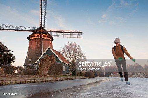 Netherlands, Woman ice skating. Wingmill : Stock Photo