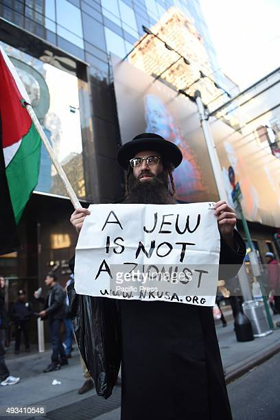 Neturei Karta member with sign denouncing Zionism Several hundred activists gathered in Times Square to show support for Palestinians amid the...