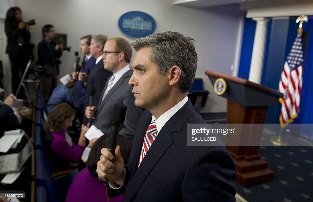 Network and cable news correspondents including CNN's Jim Acosta (C) do stand-ups prior to a press conference by US President Barack Obama in the Brady Press Briefing Room at the White House in Washington, DC, October 8, 2013, as the crisis over a US government shutdown and debt ceiling standoff deepens on the 8th day of the shutdown. AFP PHOTO / Saul LOEB