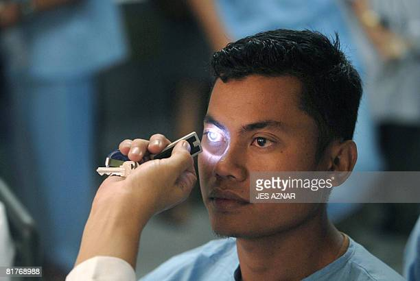 A neurologist performs an optalmologic test on a Philippine Coast Guard diver who was flown out from the site of the sunken Princess of the Stars...