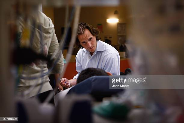Neurology fellow Dr Brill Stroud speaks with a boy after he was admitted to the emergency room on September 11 2009 at the Children's Hospital in...