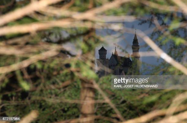 Neuschwanstein Castle is seen behind trees as dark clouds hang in the sky over Schwangau southern Germany on April 23 2017 / AFP PHOTO / dpa /...