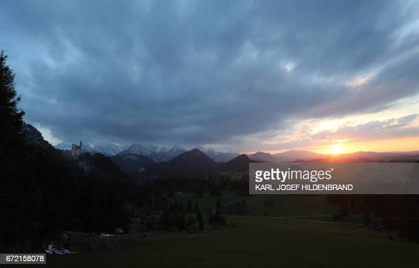Neuschwanstein Castle is seen in front of an Alps panorama as sun sets in Schwangau southern Germany on April 23 2017 / AFP PHOTO / dpa / KarlJosef...