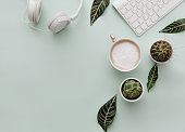 Neutral Minimalist Flat Lay Scene With coffee, keyboard, headphones and cactus