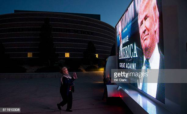 Nevada caucus voter Cecilia Perez looks up at the Donald Trump electronic billboard truck parked in front of the Palo Verde High School GOP caucus...