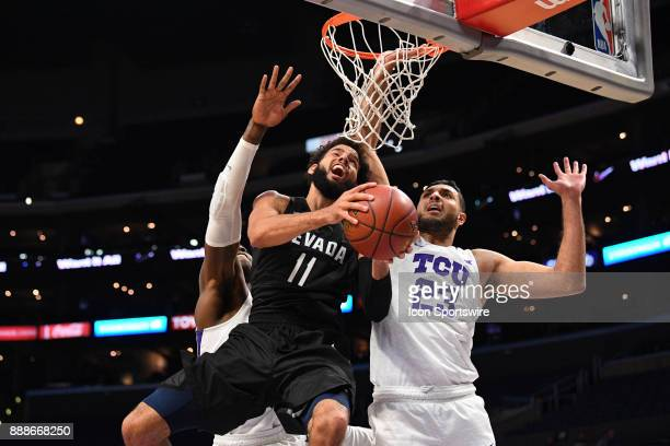 Nevada forward Cody Martin tries a difficult layup under pressure from TCU forward Ahmed Hamdy during an college basketball game between the TCU...