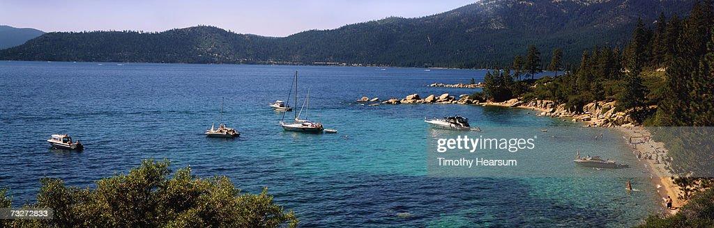 'USA, Nevada, Lake Tahoe, Sand Harbor, boats moored in lake off crowded beach' : Stock Photo