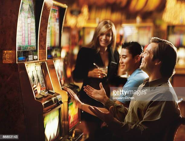USA, Nevada, Las Vegas, People in casino playing on slot machines