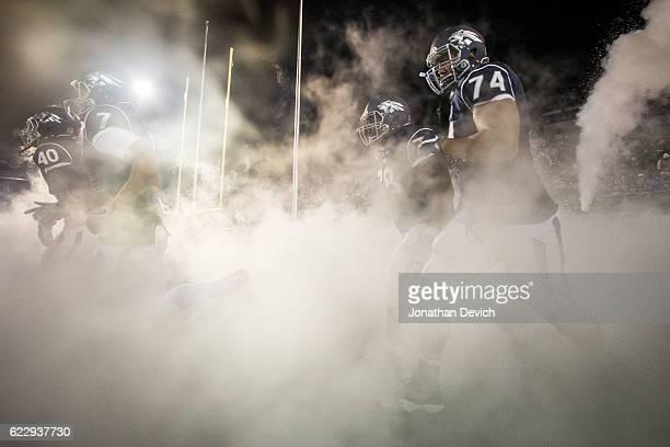 Nevada players run through the smoke for tonights game against San Diego at Mackay Stadium on November 12 2016 in Reno Nevada