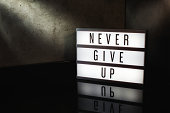 Never give up motivational message on a light box in a cinematic moody background